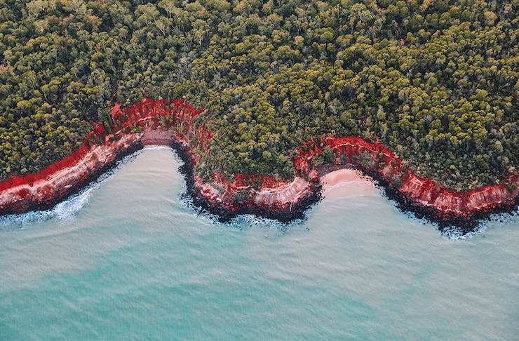 Stunning blue water meets a red sand beach, fringed by a lush bush.