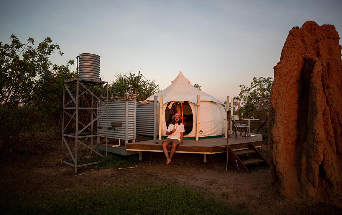 a man sits at Top End Safari Camp at dusk
