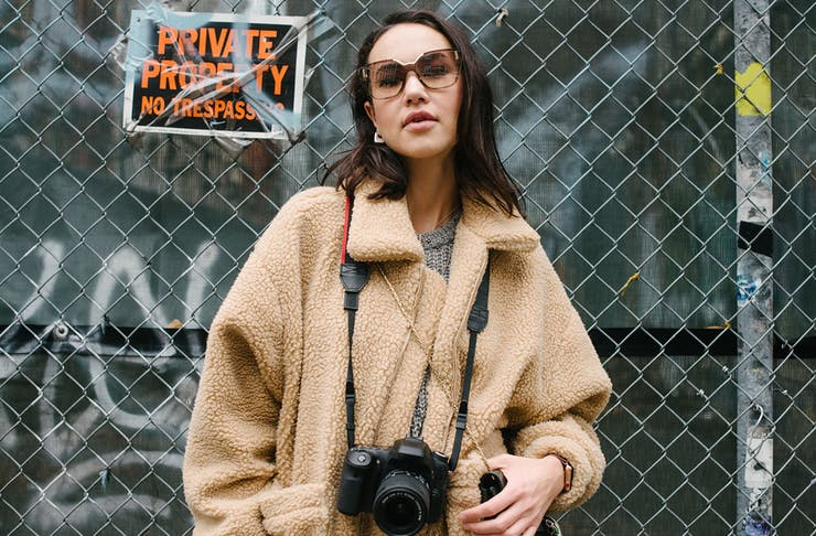 A woman, dressed in a fluffy cream jacket and vintage sunglasses, leans against a wire fence, holding a camera and handbag.