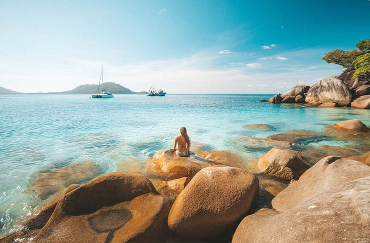 a woman sits on rocks looking out at crystal clear water and boats sailing in the distance.