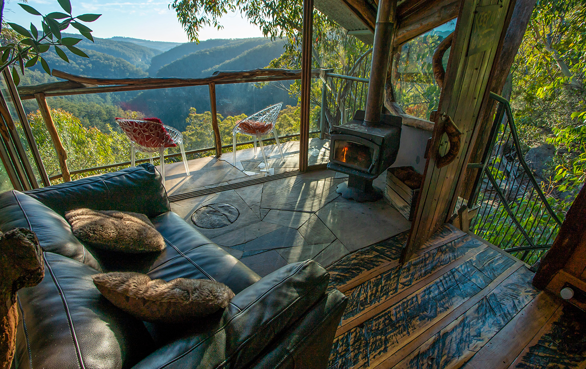 The lounge room and deck of a treehouse in the Blue Mountains