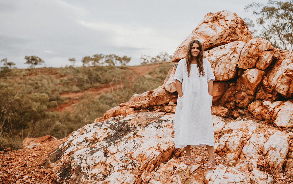 Glenda of Cungelela Art, poses on a red rock in the desert in a white dress and colourful TWOOBS.
