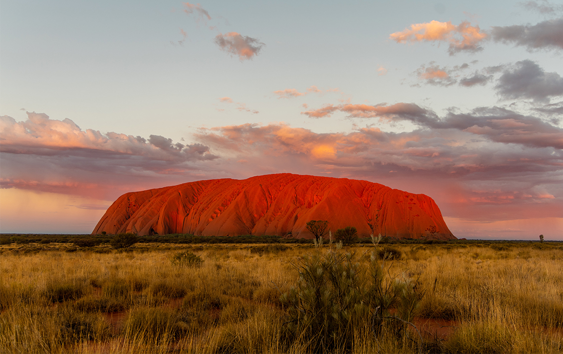 Uluru at sunset, a dusty pink and blue sky behind it.