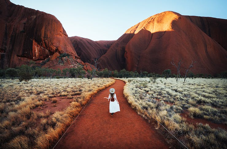 a woman in a white dress walks up to Uluru in the early morning.