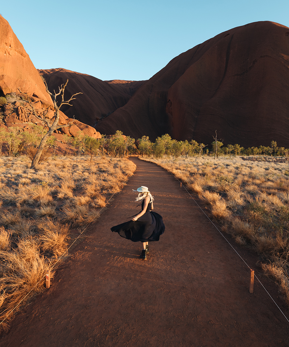 a woman in a black dress twirls in front of Uluru