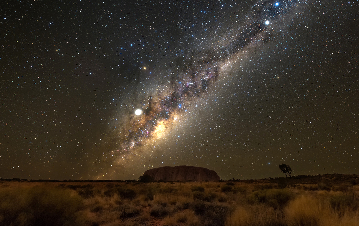 the night sky shimmers with stars over uluru at night.