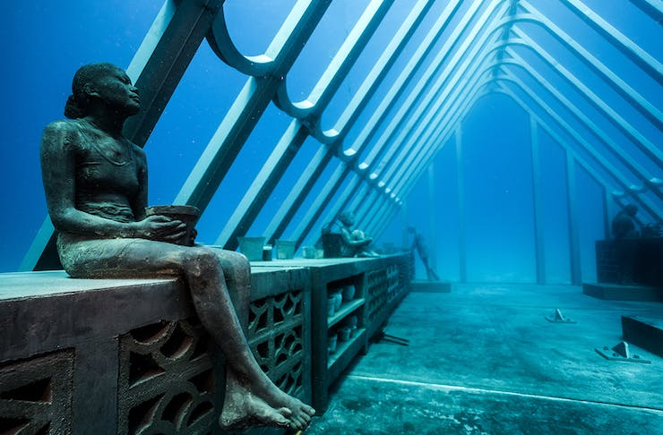 a stunning underwater sculpture featuring a woman sitting on a bench.