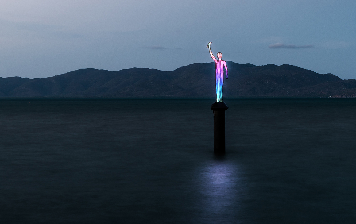a brightly coloured sculpture beams out from the middle of the ocean at dusk.