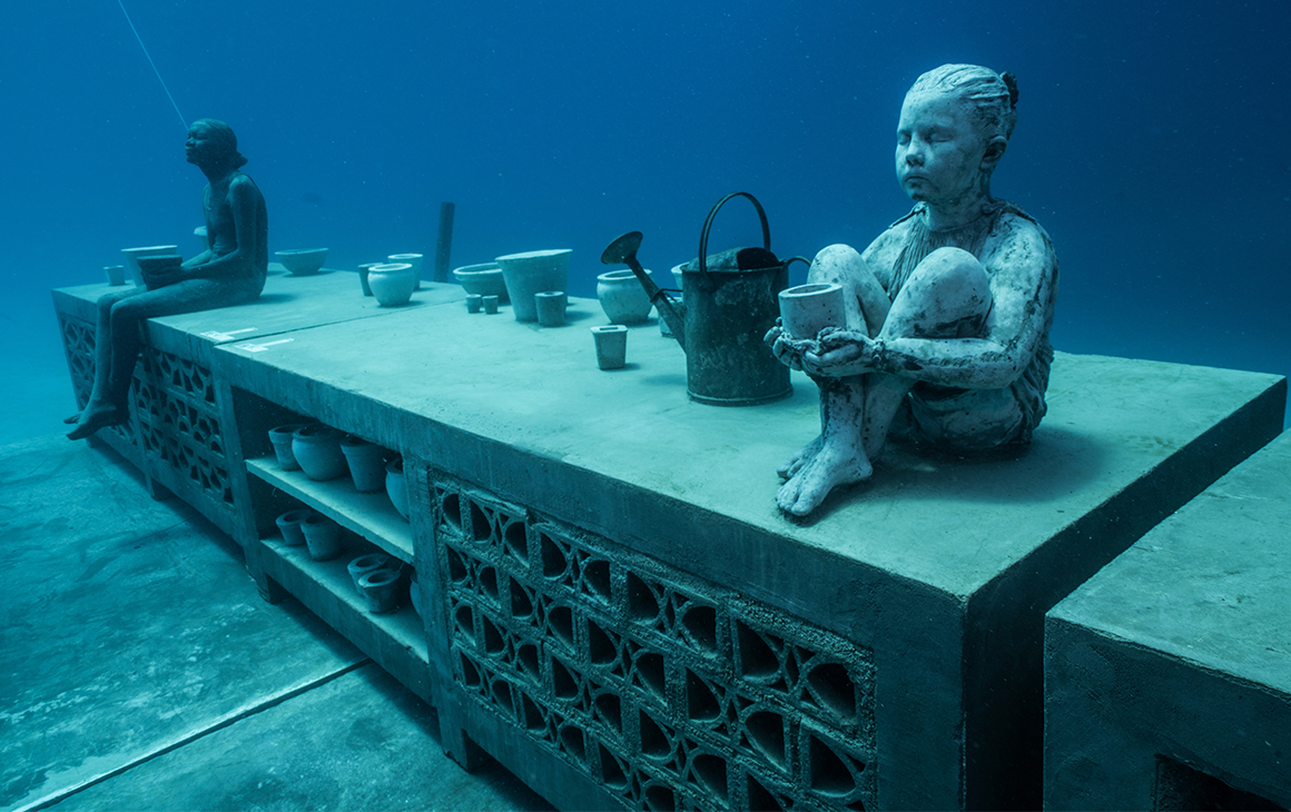 an underwater sculpture featuring a small child sitting on a bench and a woman in the backgound.