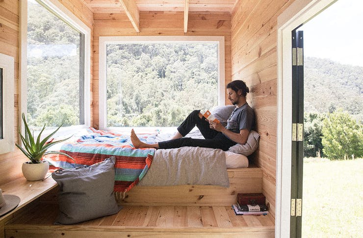 a man sits reading a book in a wooden cabin.