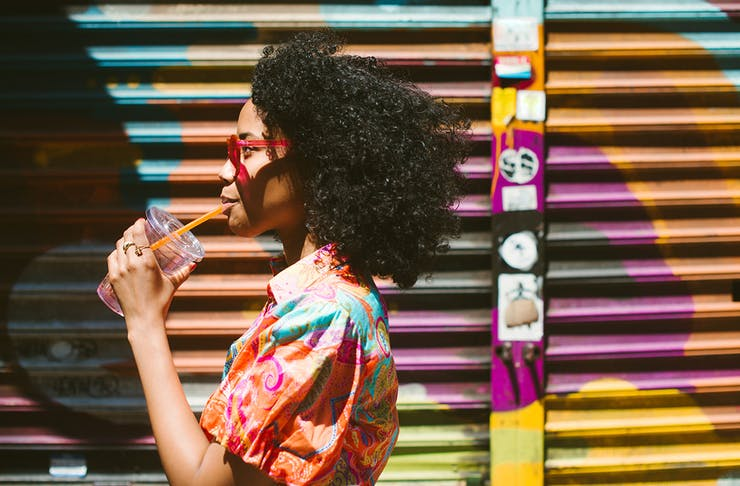 a woman wearing a colourful shirt sips on a drink while walking past a colourful wall.