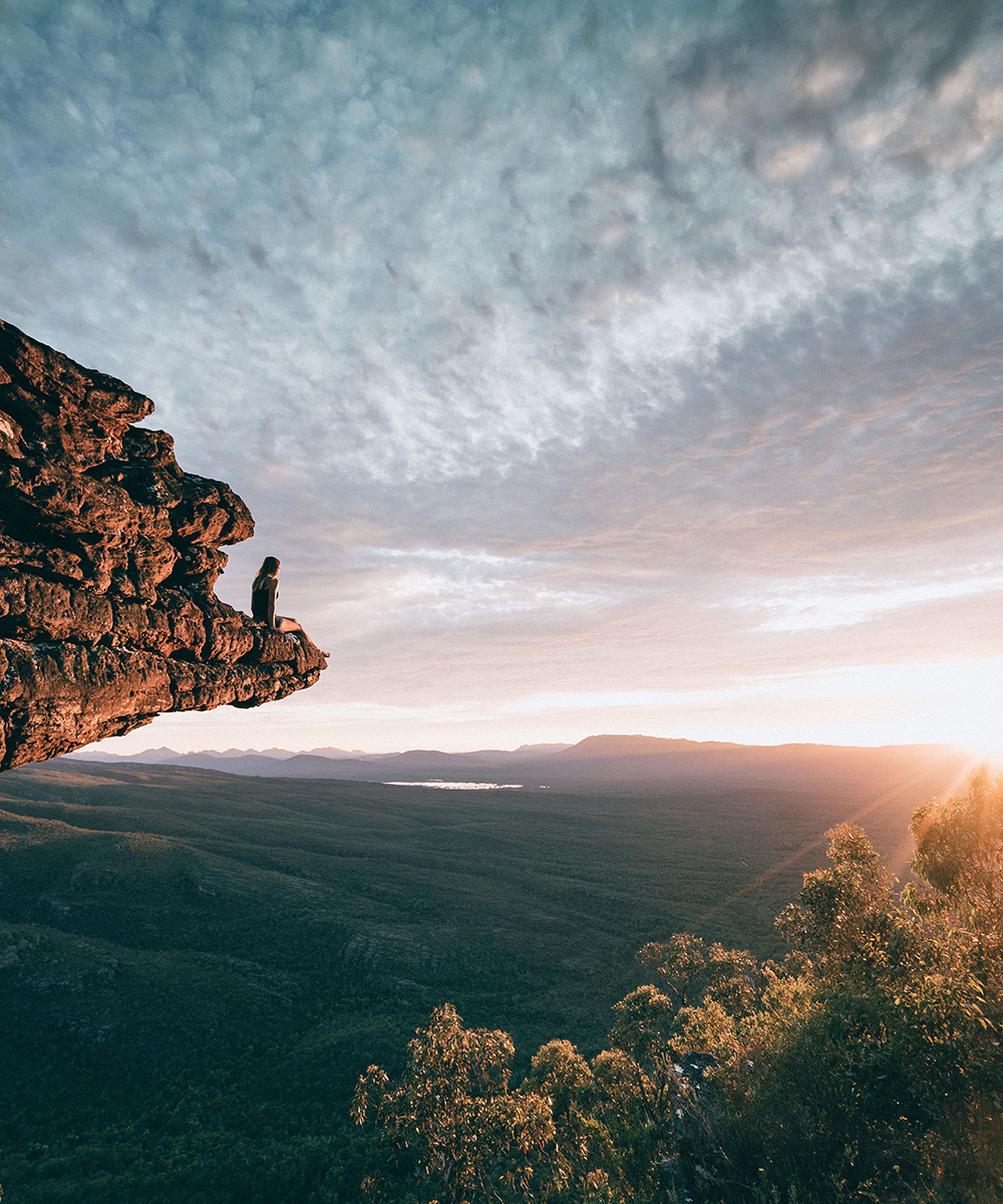 A woman sits on a rocky outcrop overlooking The Grampians