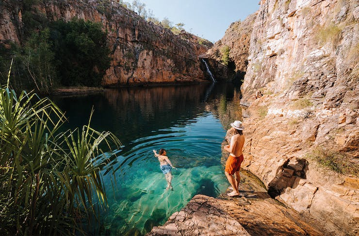 Two people swim in the clear blue waters of Maguk in Northern Territory.