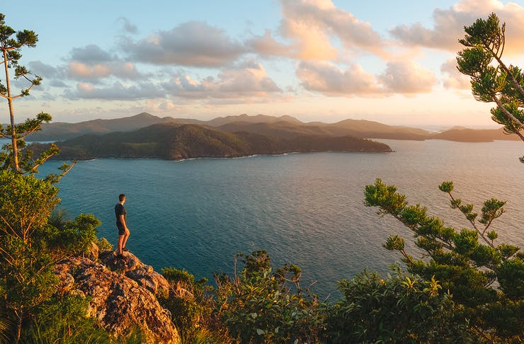A man stands on a boulder looking out a dreamy scene with  azure ocean, islands in the distance and dusty sky.