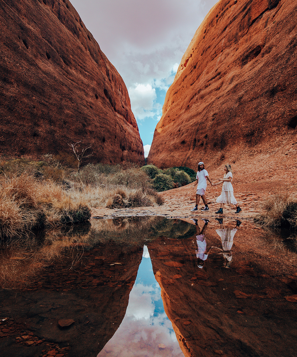 a young man and woman, dressed in white, hold hands walking through Walpa Gorge.