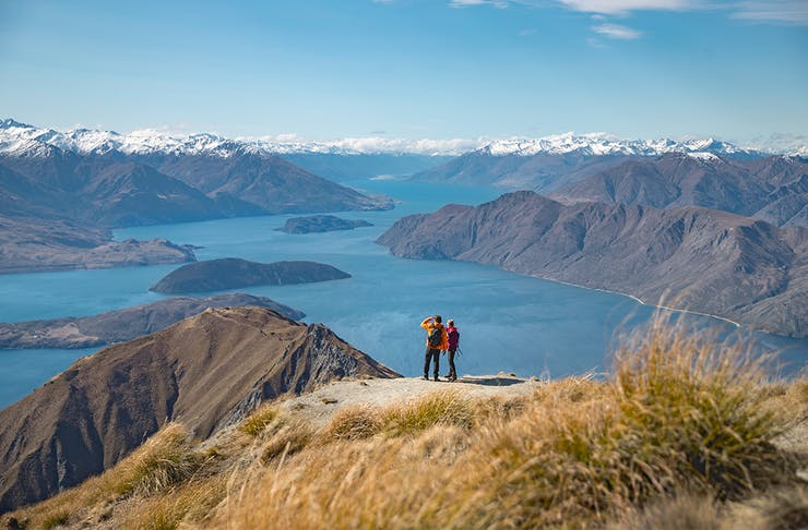 two people stand at the top of a mountain overlooking stunning lake wanaka, a brilliant blue sky in the background.