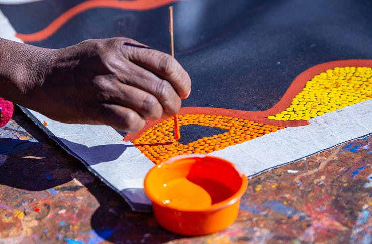 a close up of a hand creating a dot painting on a black canvas background. The dots are white, yellow and orange.
