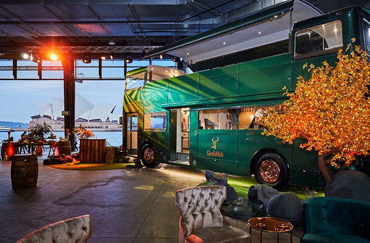 two storey vintage bus in warehouse style room with views of sydney harbour