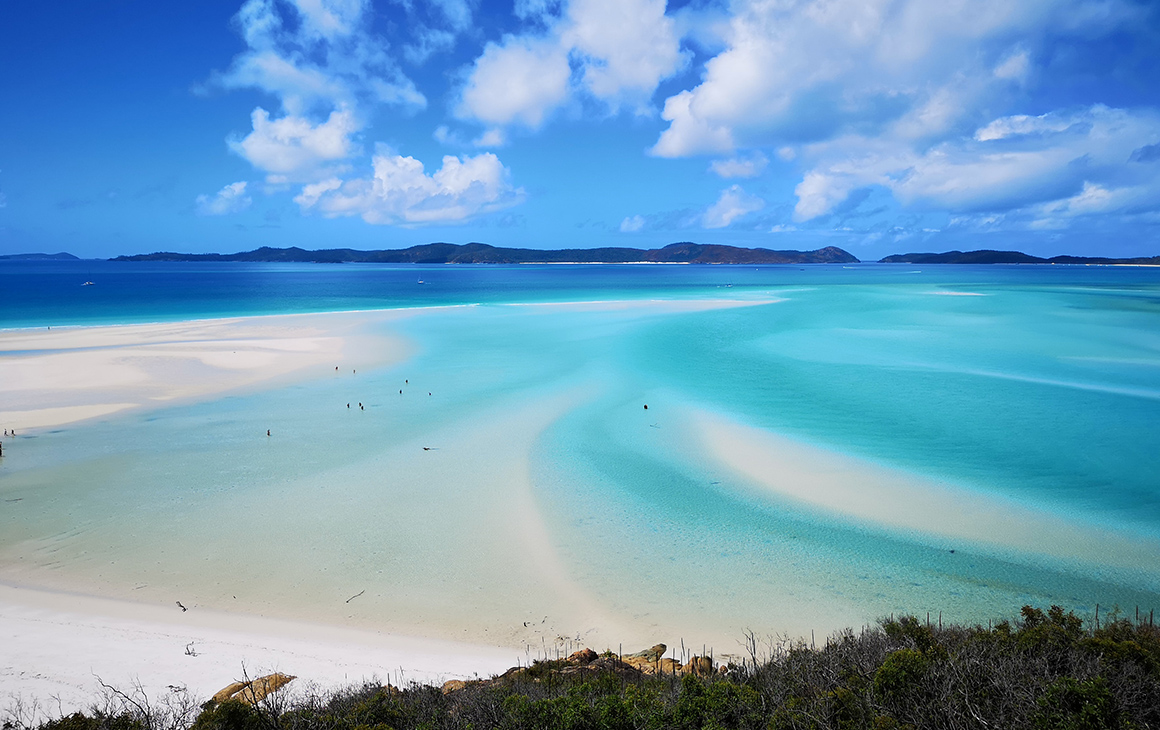 bright white sand meets azure ocean with a bright blue sky behind it.