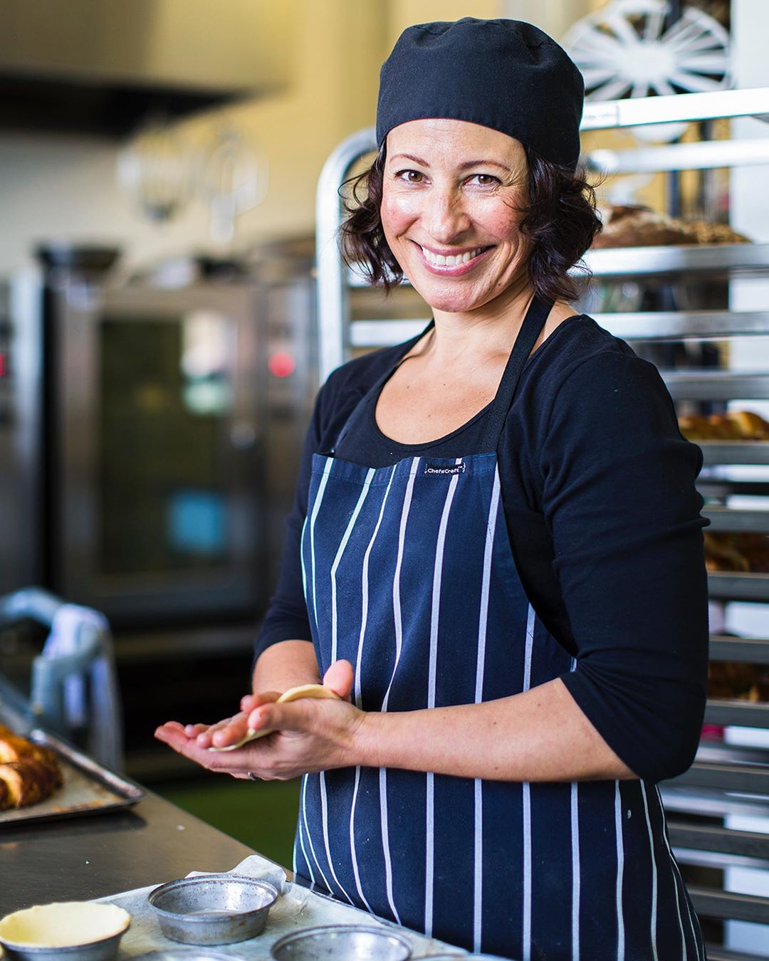 Cherie Lydon, founder of Wholegreen Bakery standing at a bench in her industrial kitchen, wearing a stripy blue apron, rolling out pie dough and smiling at the camera.