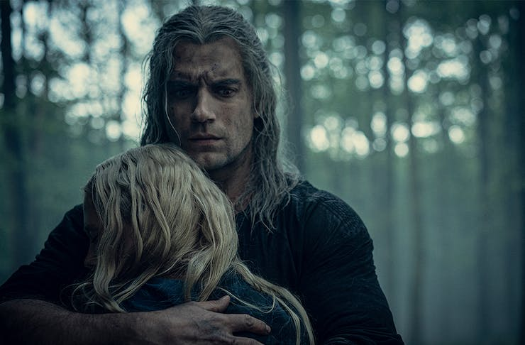 The Witcher embraces a small blonde person in the woods.