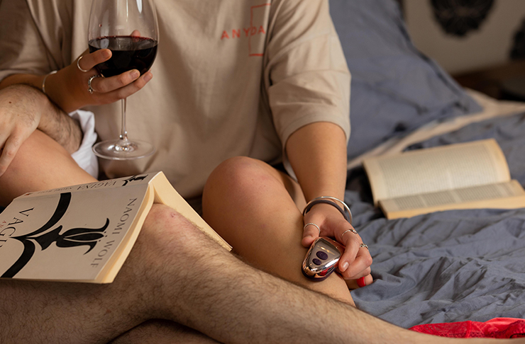 two people sitting in bed with wine and pocket vibrator