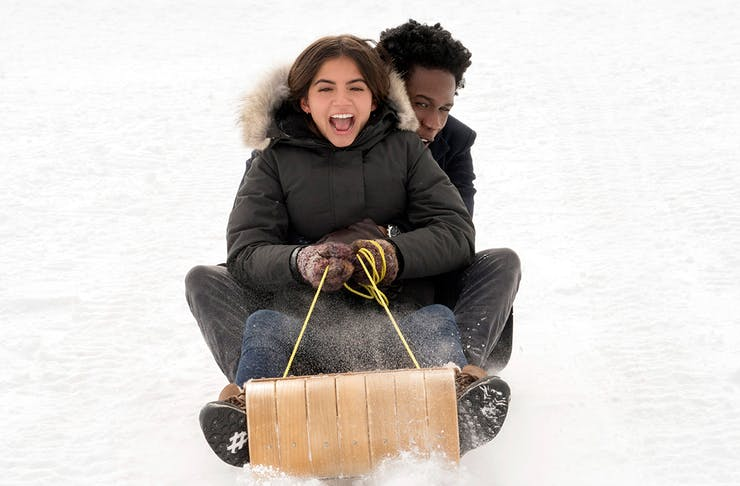 a young man and woman toboggan down a snowy mountain.