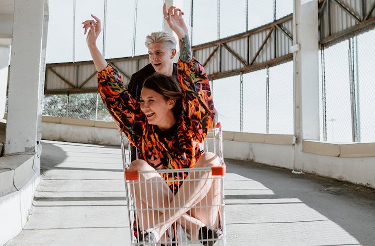 a young man pushes a woman in a trolley around a carpark. She has her hands up in the air, laughing.