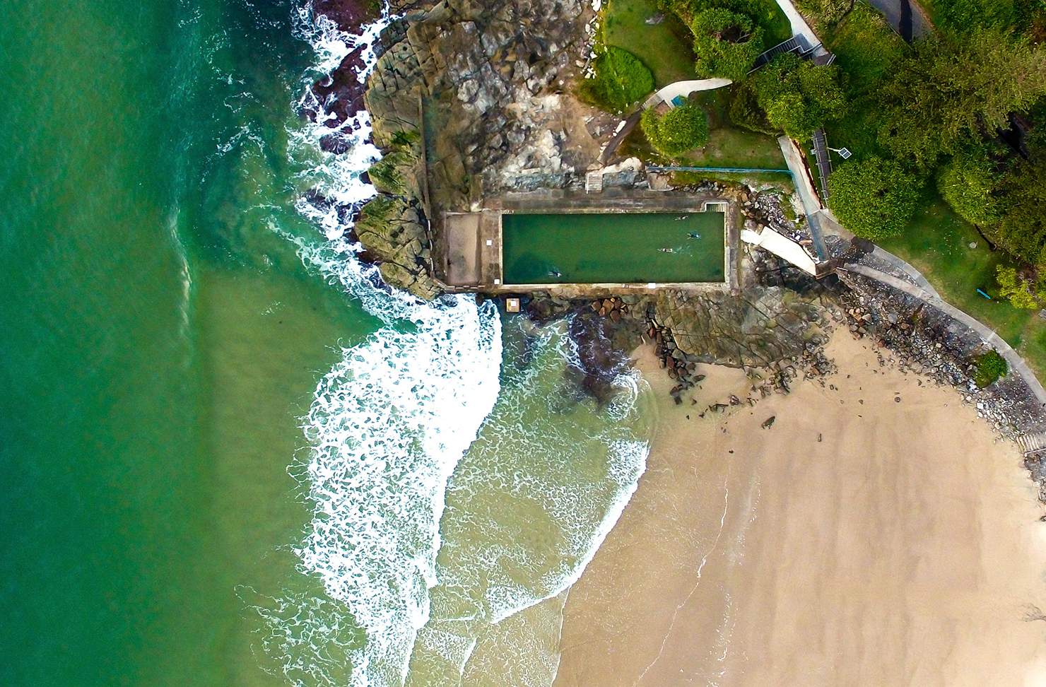 a bird's eye view of Main Beach at Yamba and the sparkling ocean pool.