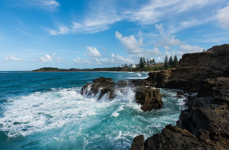 a stunning view of Yamba from Main Beach with waves crashing onto the rocks and the town sits in the distance.