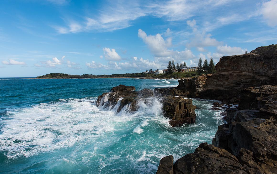 waves crash onto the cliffs at yamba