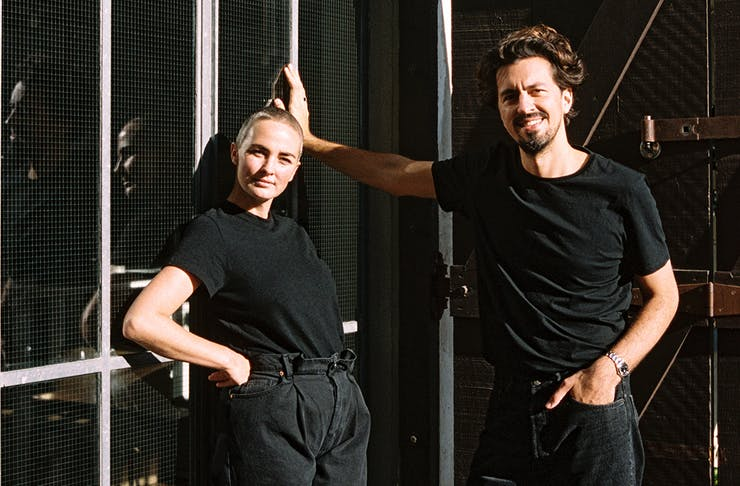 Youswim founders, dressed in black, pose against a wall.
