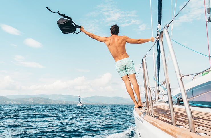 a man holds onto the side of a boat holding a backpack in the air.